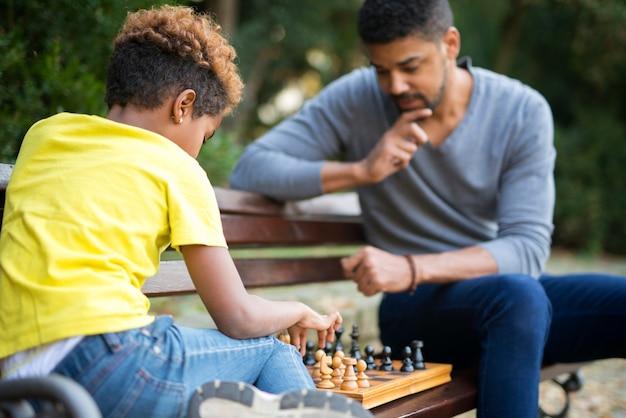 Отец и дочь играют в шахматы на скамейке в городском парке