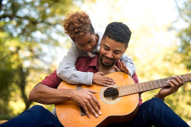 一緒にギターを弾く父と娘