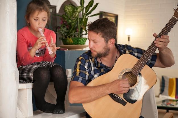 Отец и дочь играют на музыкальных инструментах