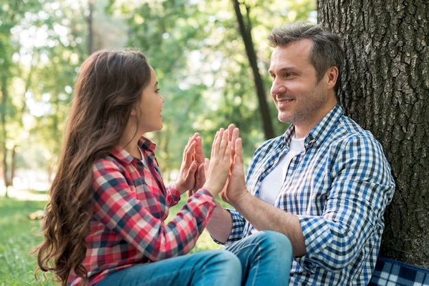 父と娘が公園で座っている間にケーキケーキゲームをプレイ
