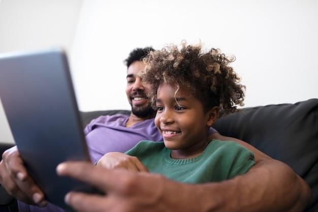 Отец и дочь, играя планшетный компьютер на софе в гостиной.