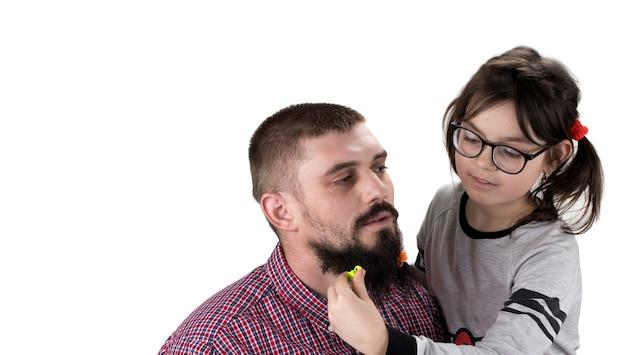 Отец и дочь играют вместе. девушка играет со своим отцом и делает ему прическу. изолированные на белом.