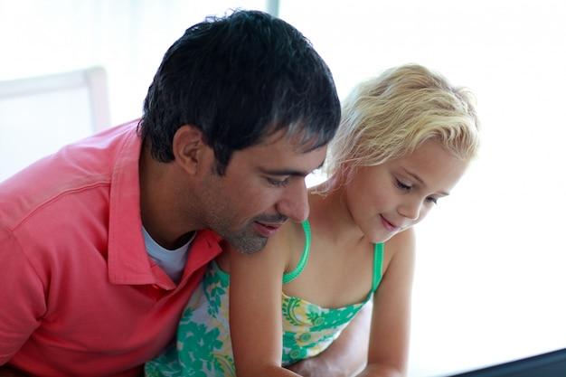 ラップトップで遊ぶ父と娘