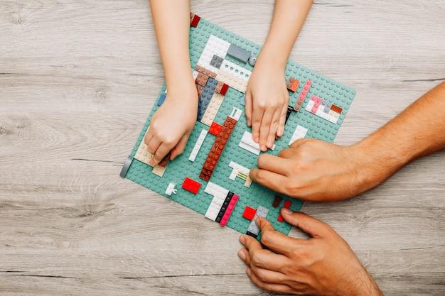父と娘の軽い木製のレゴで遊んで
