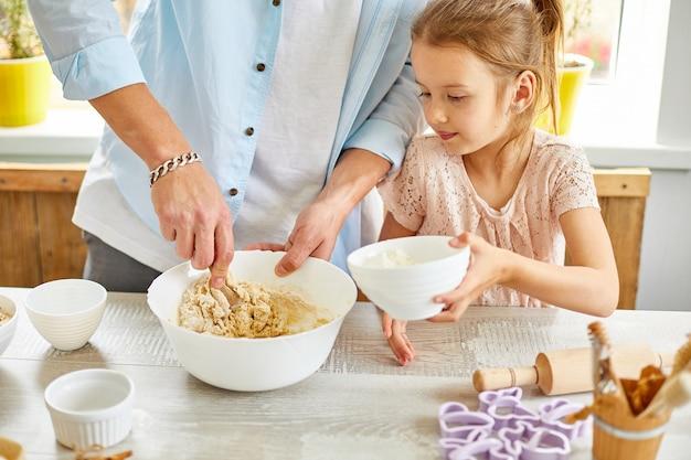 父と娘が一緒にキッチンで生地を準備する、家庭での家族の料理、父性と家族の週末のコンセプト。