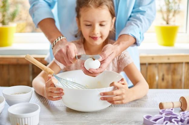 Отец и дочь вместе готовят тесто на кухне во время приготовления выпечки дома