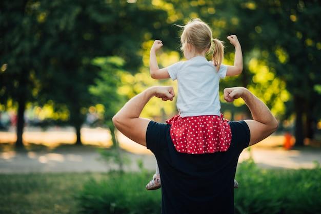 父と娘が自分の筋肉を見せて