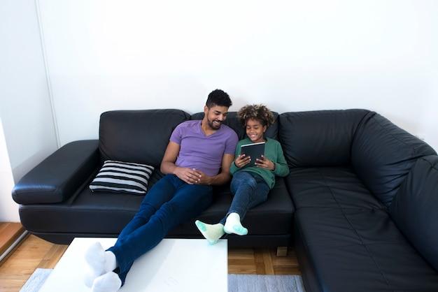 Отец и дочь, сидя на удобном диване и глядя на планшетный компьютер.