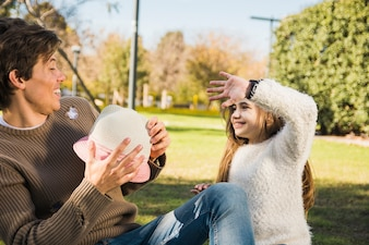Father and daughter sitting in park playing with hat