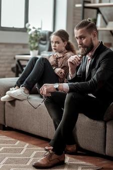 父と娘。神経質な喧嘩の後、心配した父と娘がソファに座ってストレスを感じた