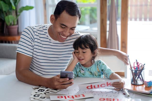 スマートフォンを使って一緒に勉強する父と娘