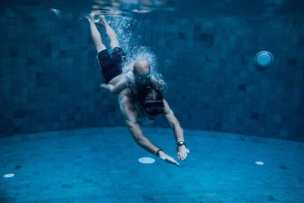 プールで一緒に泳ぐ父と娘