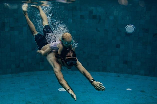 Отец и дочь вместе плавают в бассейне
