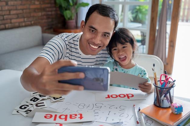 父と娘がスマートフォンを使用して一緒に自分撮りを取る