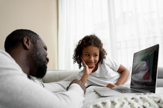 ノートパソコンで映画を見ている父と娘