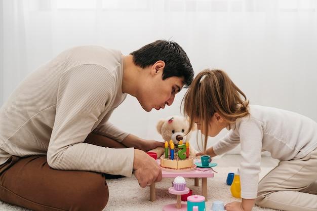 家でおもちゃを持つ父と娘