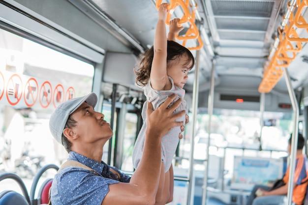 ハンドルバーにぶら下がっている公共交通機関に乗って遊んでいる父と娘