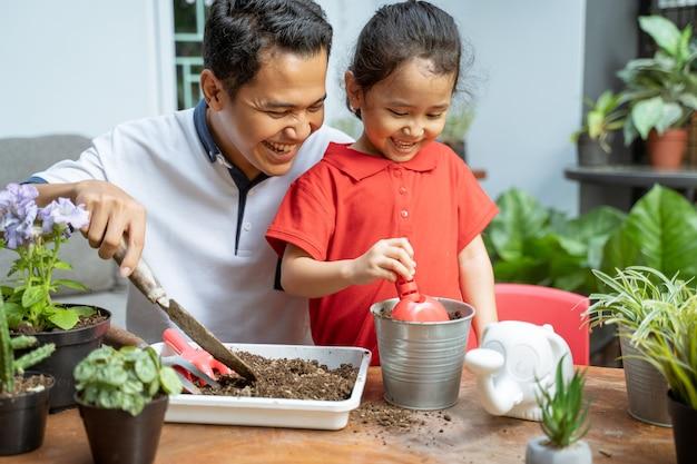 父と彼の娘たちは鉢植えの植物を植えています