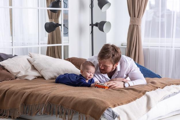 아버지와 그의 작은 아기가 침대에 누워 미니 밴 장난감 자동차를 가지고 노는