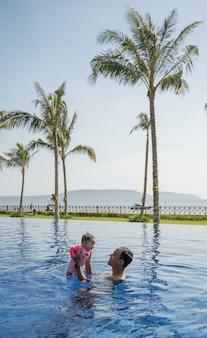 父と彼の小さな赤ちゃんは水泳を楽しむ