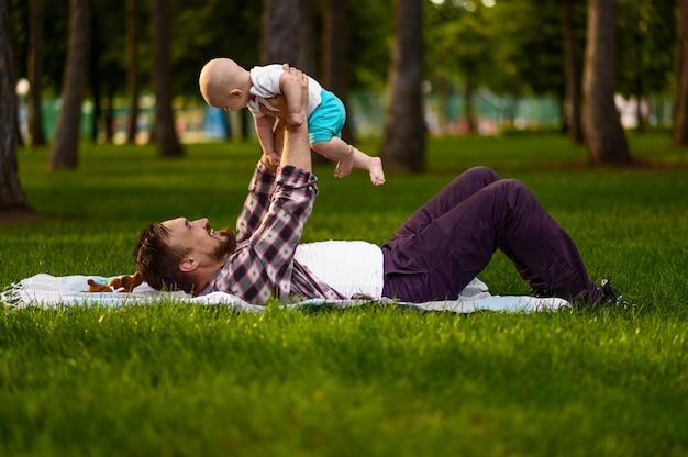 아버지와 그의 작은 아기 여름 공원에서 잔디에 누워