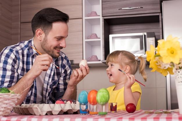 Отец и его маленький ребенок рисуют пасхальные яйца