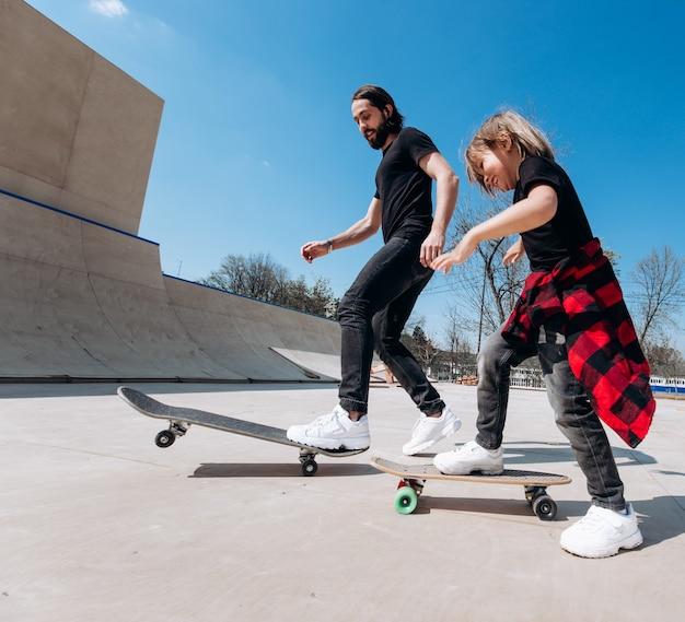 캐주얼한 옷을 입은 아버지와 어린 아들은 화창한 날 미끄럼틀이 있는 스케이트 공원에서 스케이트보드를 탄다.