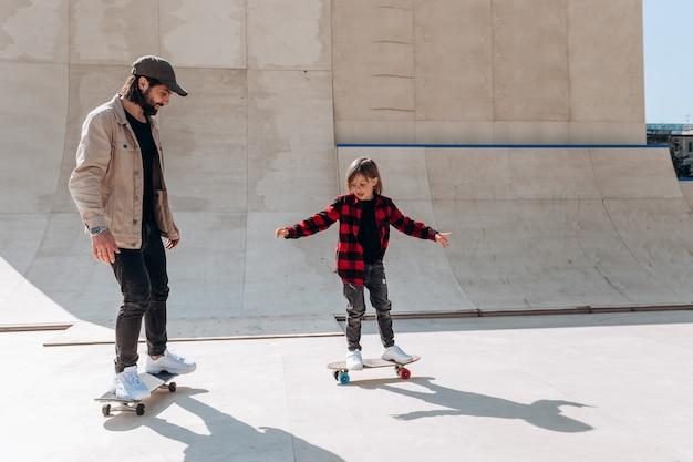 캐주얼한 옷을 입은 아버지와 그의 어린 아들은 화창한 날 밖에 미끄럼틀이 있는 스케이트 공원에서 스케이트보드를 탄다.