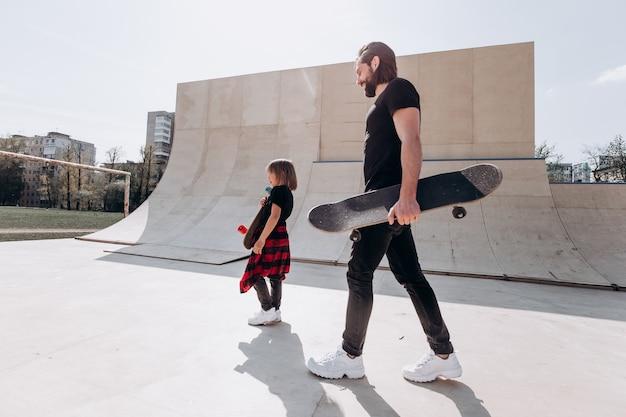 세련된 캐주얼 옷을 입은 아버지와 그의 어린 아들은 화창한 날 스케이트 공원에서 스케이트보드를 손에 들고 걷습니다.