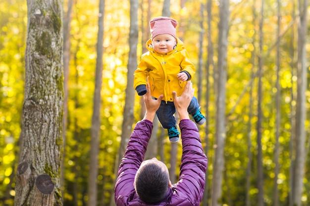 Отец и его маленький сын веселятся в осеннем парке