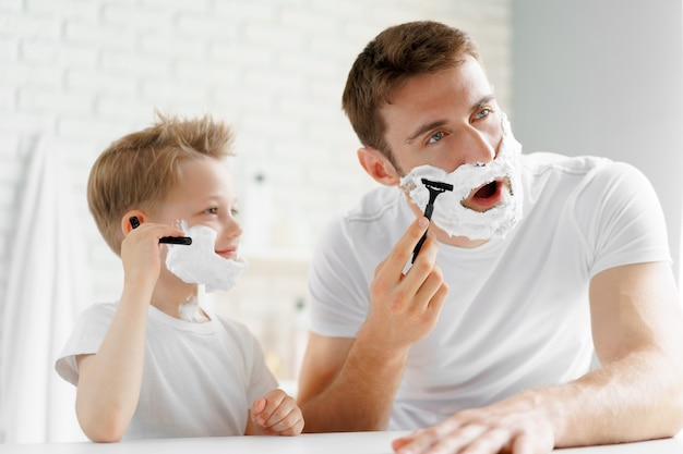 아버지와 그의 작은 아들이 함께 욕실에서 면도