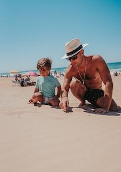 Отец и его сын счастливо играют на песчаном пляже