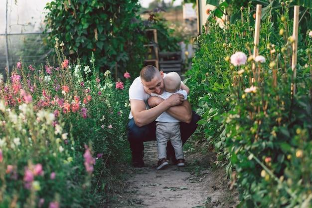 Отец и его сын играют и обнимаются на открытом воздухе.