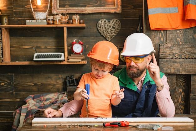 木製のワークショップで一緒に働いている父と彼の息子。初期の開発。子供の成長。