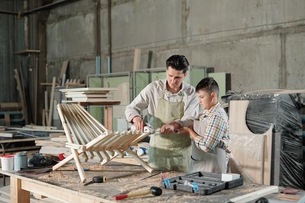 道具と削りくずを持って机に立って、ワークショップの長椅子のために板に参加するエプロンの父と彼の10代の息子