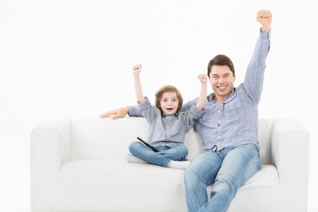 Отец и его маленький сын, улыбаясь на диване