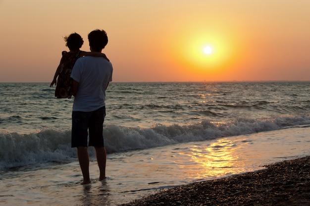 Отец и ребенок на пляж заката.