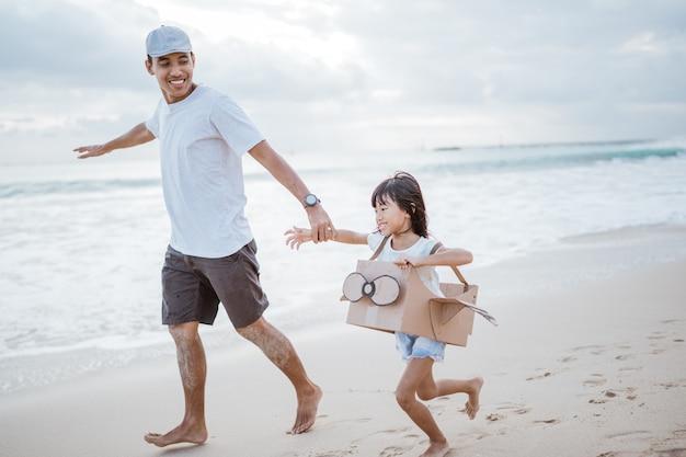 ビーチでおもちゃの段ボール飛行機で走っている父と子
