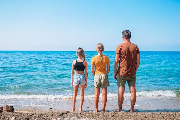 父と子供たちがビーチで夏の休暇を楽しんで