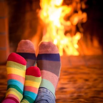 暖炉のそばのクリスマスソックスで父と子供の足家でリラックスする家族冬休み