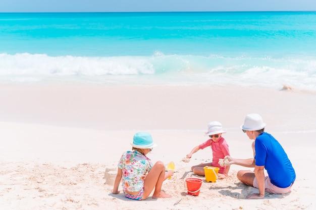 아버지와 열 대 해변에서 모래성을 만드는 아이. 해변 장난감을 가지고 노는 가족