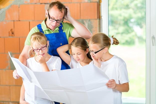 Отец и дети или дочери и друзья, глядя на план строительства на строительной площадке