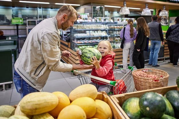 Отец и дочка выбирают арбуз в супермаркете