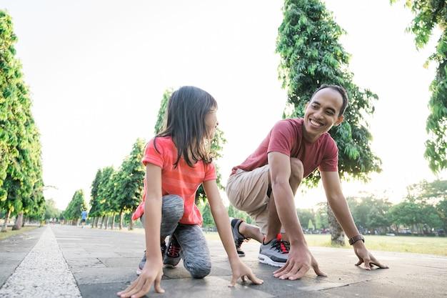 Отец и дочка делают упражнения на открытом воздухе здорового образа жизни семьи с ребенком