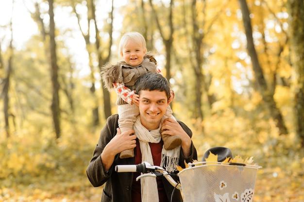 父と娘は同じ自転車で楽しんでいます。秋の写真撮影。