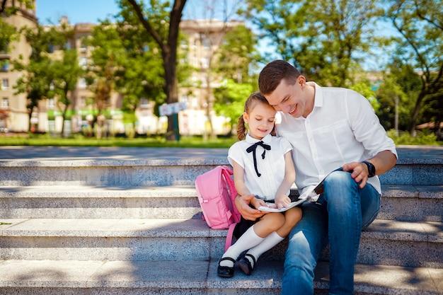 父と小さな娘が階段に座って本を読む