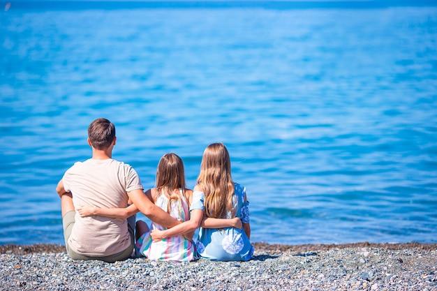 Отец и маленькие девочки на пляже веселятся на летних каникулах