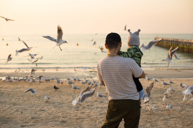 Отец и маленький сын кормить чаек на закате пляже в дубае. мужчина с мальчиком кормит птиц на пляже
