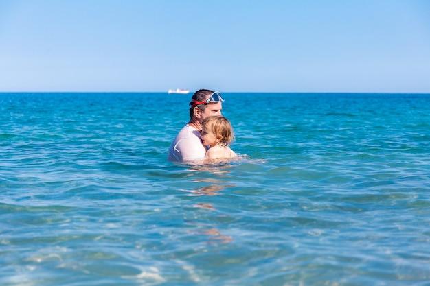 Отец и маленький сын весело плавают и играют вместе в морской воде на летних каникулах