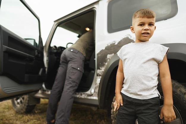 ロードトリップで車の近くに立っている父と幼い息子